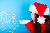 Asian little girl in Santa Claus hat blowing snowflakes