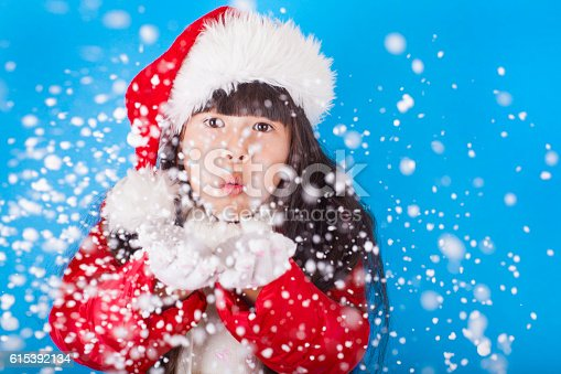 istock Asian little girl in Santa Claus hat blowing snowflakes 615392134