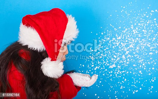 istock Asian little girl in Santa Claus hat blowing snowflakes 615392164
