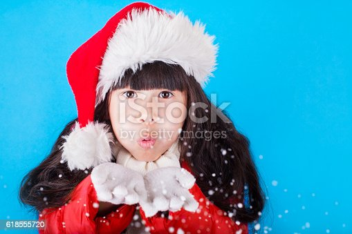 istock Asian little girl in Santa Claus hat blowing snowflakes 618555720