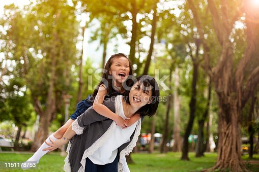 Asian little girl on a piggy back ride with her mother in park Taipei