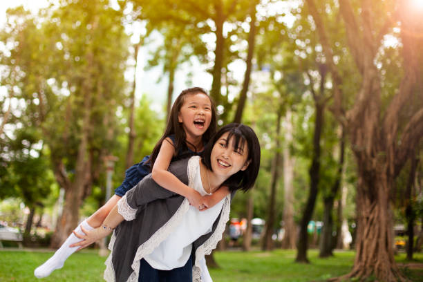 Asian little girl on a piggy back ride with her mother in park Taipei Asian little girl on a piggy back ride with her mother in park Taipei vietnamese ethnicity stock pictures, royalty-free photos & images