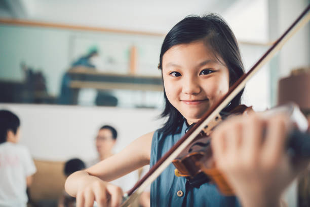 Asian Little Girl playing violin at home. stock photo
