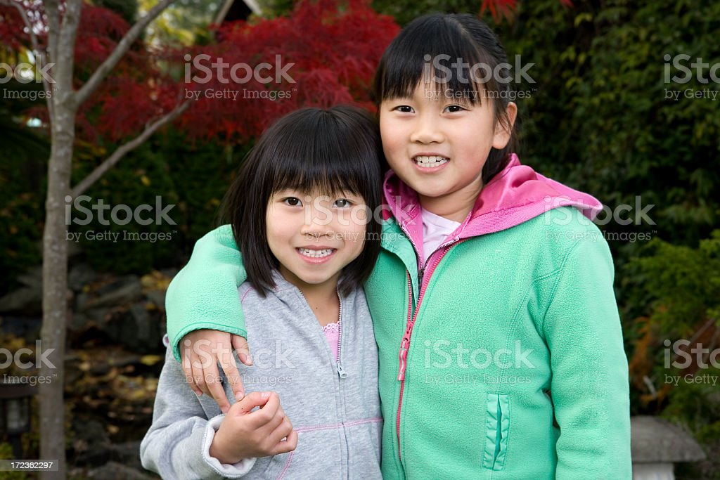 Asian Little Girl Sisters Embracing for Portrait Outdoors, Copy Space royalty-free stock photo