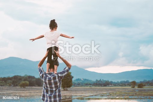 Back view of asian little girl standing on father's shoulder and playing together in the cornfield in vintage color tone