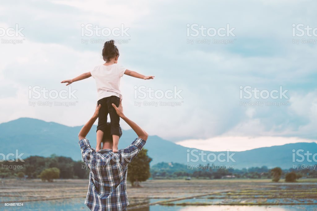 asian little girl standing on father's shoulder and playing together stock photo