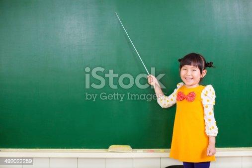 istock asian little girl using a baton to point on a blackboard 492022289
