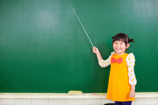 istock asian little girl using a baton to point on a blackboard 492022289