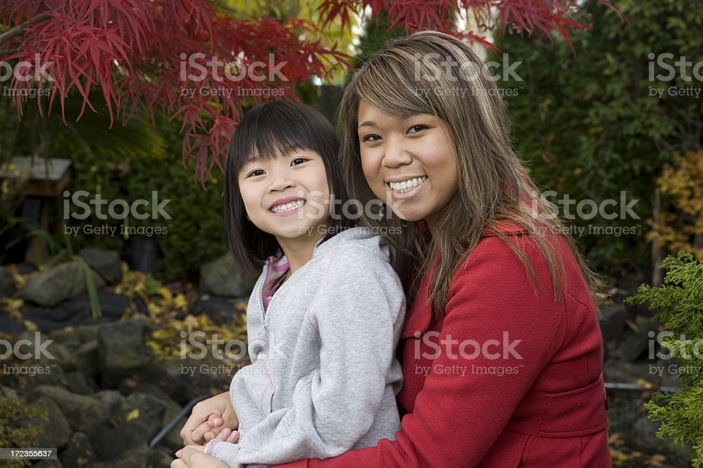 Niña asiática con más hermana posando para retratos al aire libre foto de stock libre de derechos