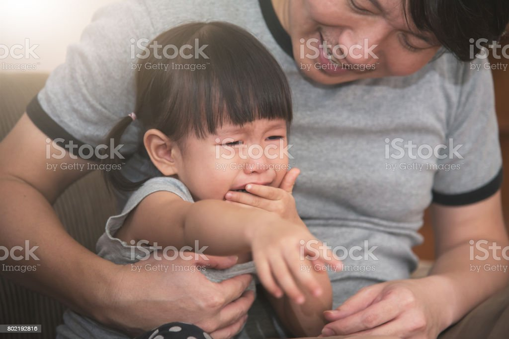 Asian little kid girl crying while father consoling. stock photo