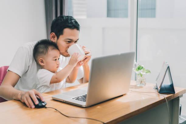 asiatischen kleinen sohn half vater kaffeetrinken zwischen der arbeit mit laptop computer notebook am arbeitsplatz glückliche familie zusammen zu hause konzept. - genderblend stock-fotos und bilder