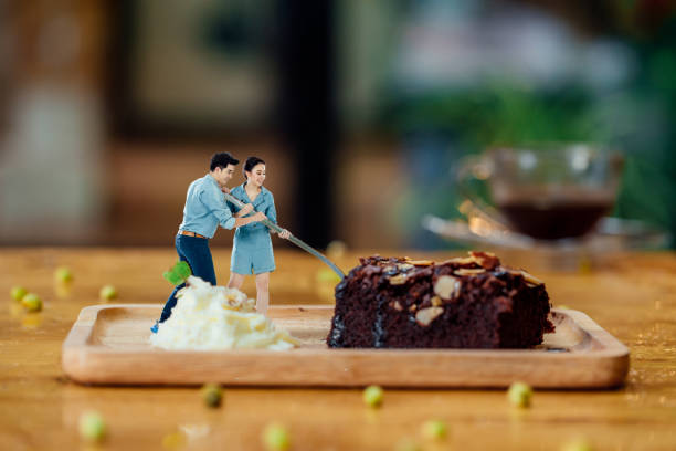 Asian lovers are trying to scoop a black cake with spoon together happily and funny. stock photo