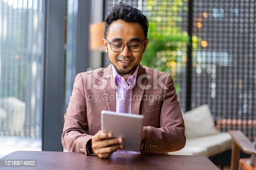 Asian Malay businessman working with digital tablet.