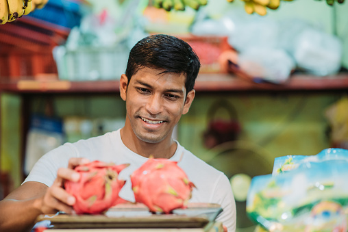 Asian malay male fruit shop owner measuring weight of two dragon fruit by weight scale at his fruit shop with smiling face