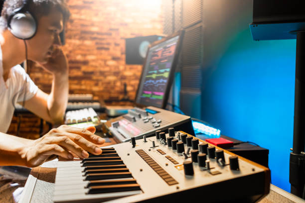 asian male composer playing midi keyboard synthesizer for making music in sound studio asian male composer playing midi keyboard synthesizer for making music in sound studio recording studio stock pictures, royalty-free photos & images