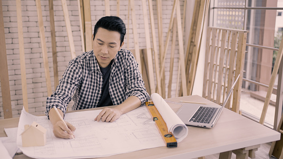 Portrait shot of a asian architect man drawing on print construction project with pencil on desk