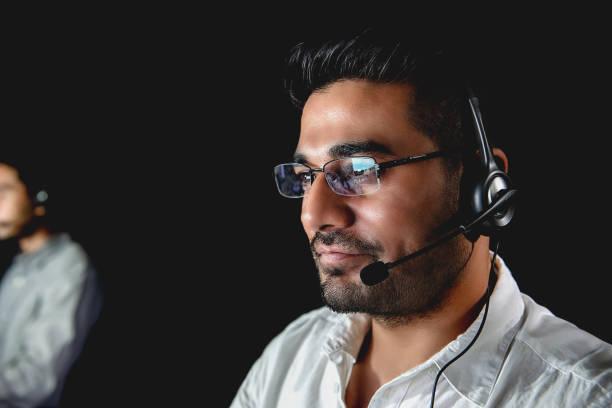asian male customer service  operators working night shift in call center - shifts call centre foto e immagini stock