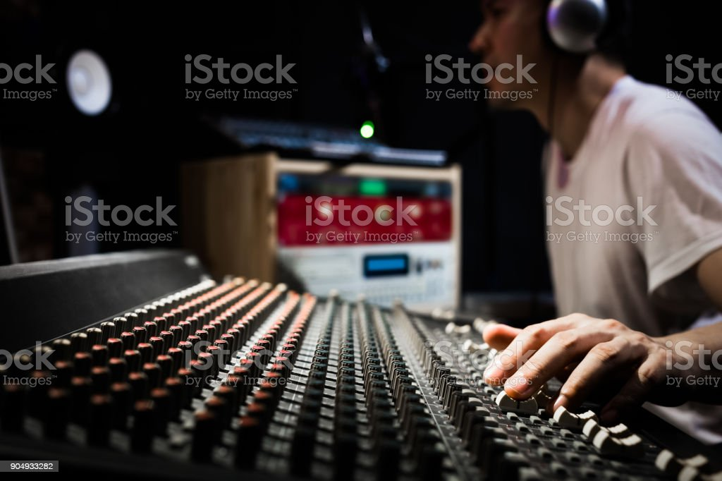 asian male dj, sound engineer, music producer working on sound mixer in recording, broadcasting studio. focus on hands stock photo