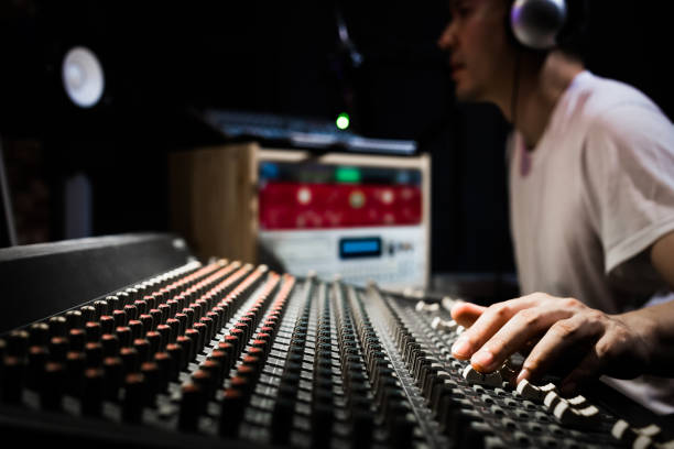 asian male dj, sound engineer, music producer working on sound mixer in recording, broadcasting studio. focus on hands asian male dj, sound engineer, music producer working on sound mixer in recording, broadcasting studio. focus on hands radio dj stock pictures, royalty-free photos & images
