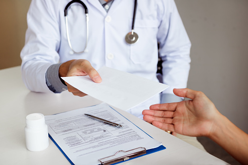 istock Asian male doctor handing a prescription to the patient. 1135078861