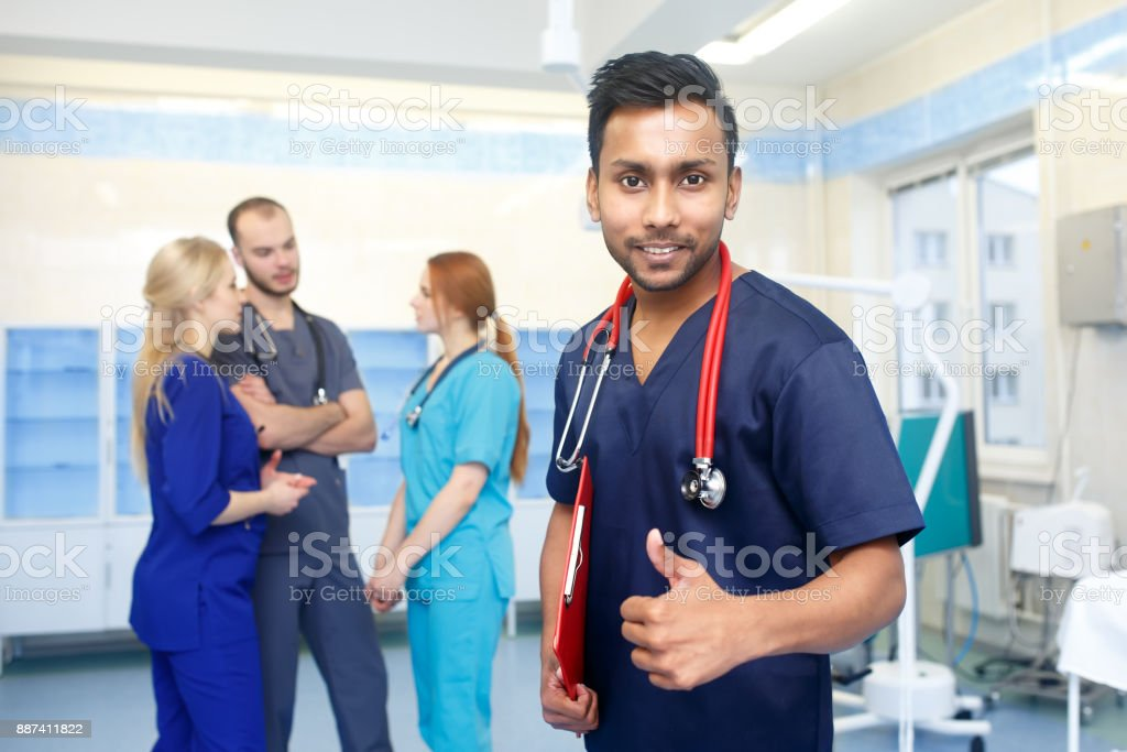 Asian male doctor in front of team, looking at camera, show thumb up, with medical team in background. Multiracial team of young doctors in a hospital standing in a operating room stock photo