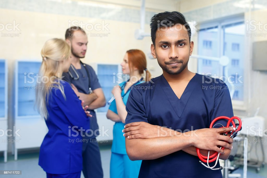 Asian male doctor in front of team, looking at camera with medical team in background. Multiracial team of young doctors in a hospital standing in a operating room stock photo