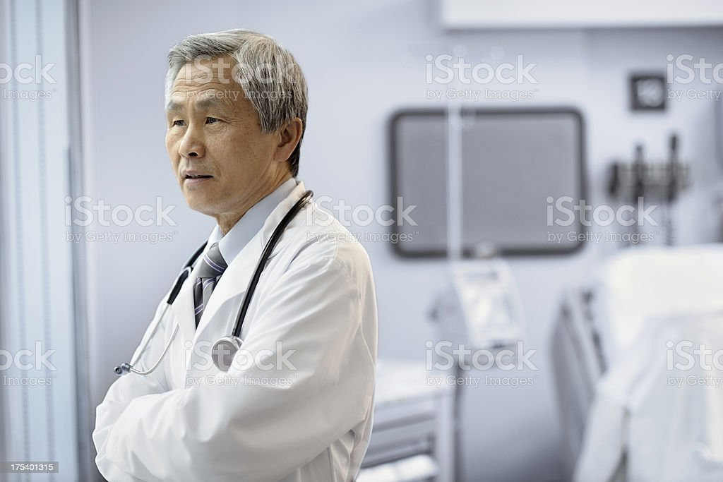 Asian male doctor looking out hospital room window. royalty-free stock photo