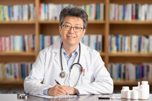 Asian male doctor sitting at desk smiling stock photo