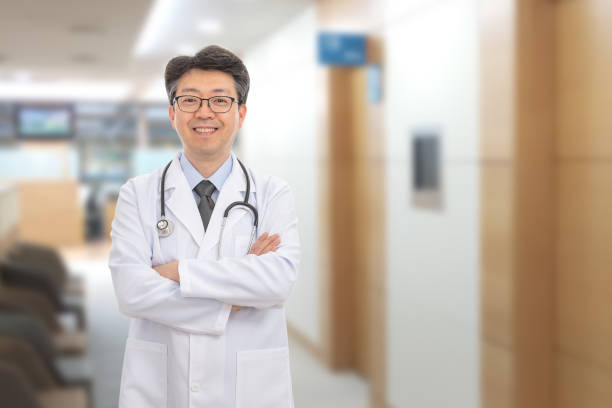 Asian male doctor smiling in the background of the hospital stock photo