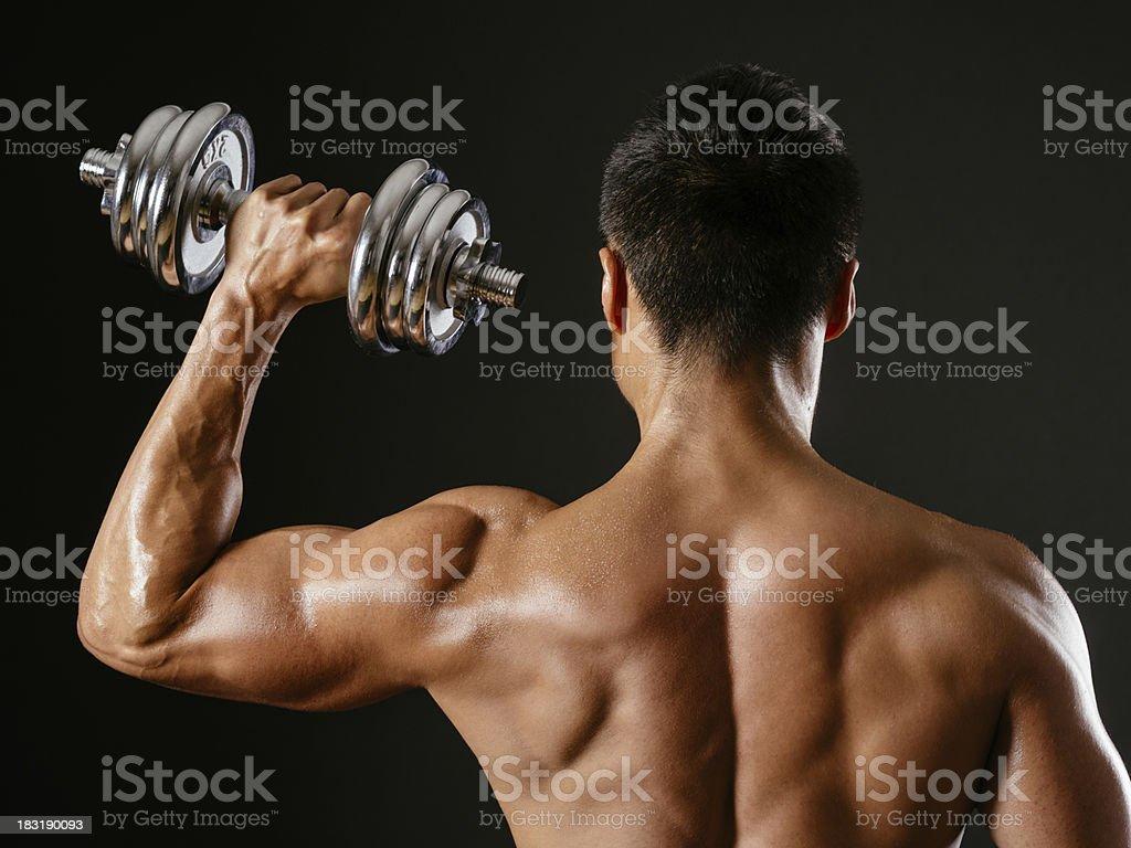 Asian male doing single shoulder press stock photo