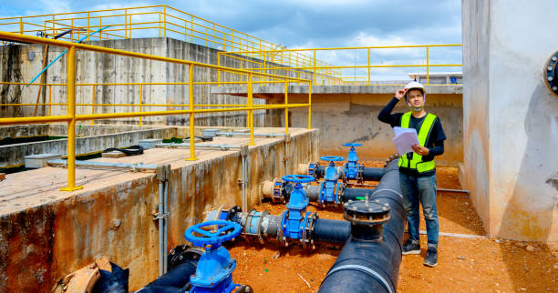 Asian Male engineering working with a tablet laptop at sewage treatment plant Asian Male engineering working with a tablet laptop at sewage treatment plant sewage treatment plant stock pictures, royalty-free photos & images