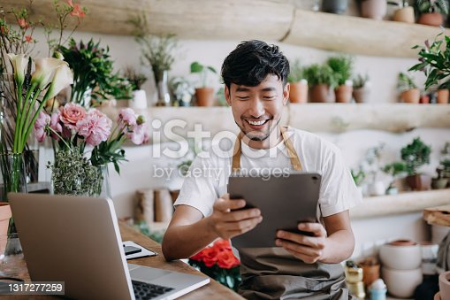 istock Asian male florist, owner of small business flower shop, using digital tablet while working on laptop against flowers and plants. Checking stocks, taking customer orders, selling products online. Daily routine of running a small business with technology 1317277259