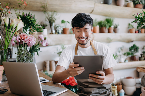Asian male florist, owner of small business flower shop, using digital tablet while working on laptop against flowers and plants. Checking stocks, taking customer orders, selling products online. Daily routine of running a small business with technology