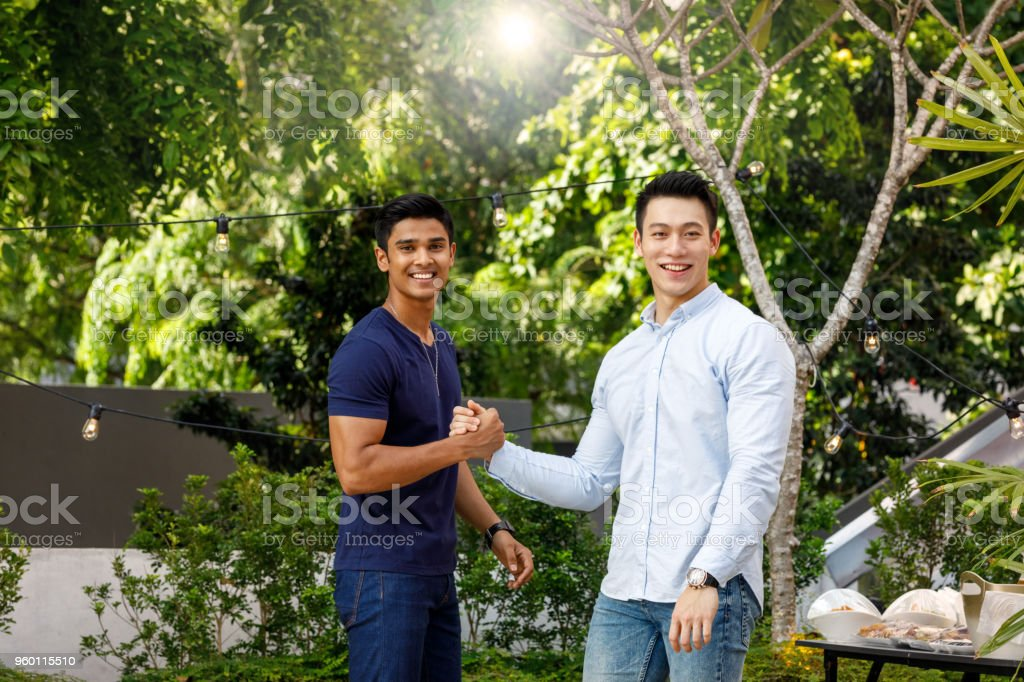 Asian Male Friends Greeting Each other at Outdoor Roof Top Party stock photo