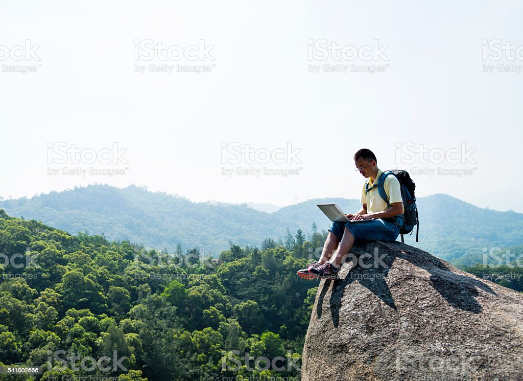 Asian male hiker using laptop on rock stock photo