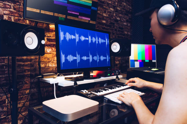 asian male hipster sound engineer working on computer in digital audio & video editing post production studio stock photo
