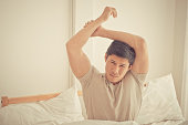Asian male is stretching out after woke up on bed