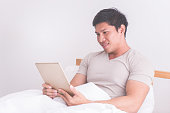 Asian male is using digital tablet on his white bed
