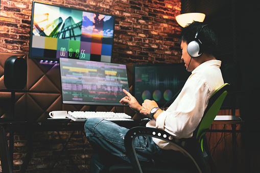 asian male media content creator editing video footage on computer in home studio