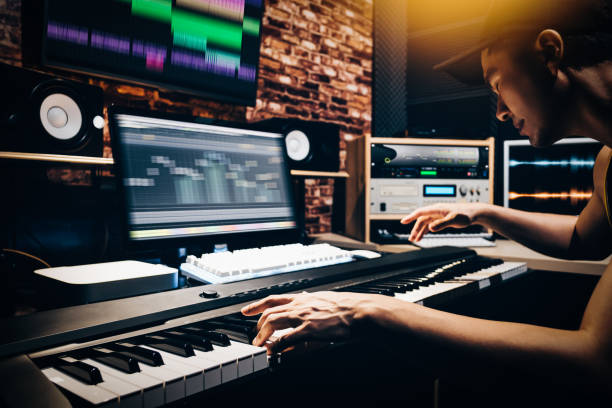 asian male music arranger hands composing song on midi piano & professional audio equipment in digital recording studio asian male music arranger hands composing song on midi piano & professional audio equipment in digital recording studio producer stock pictures, royalty-free photos & images