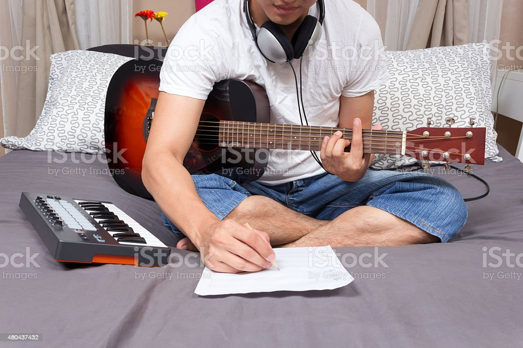 asian male music composer, musician writing song & playing guitar on...
