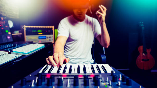 asian male music producer, dj making electronic dance music in sound studio asian male music producer, dj making electronic dance music in sound studio synthesizer stock pictures, royalty-free photos & images