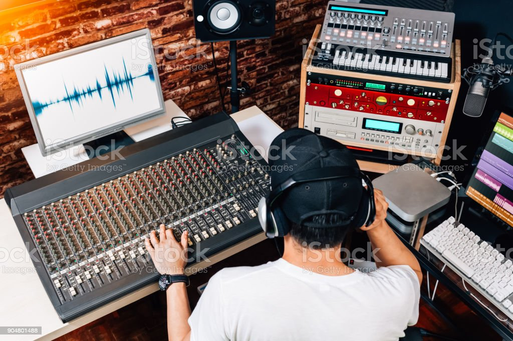 asian male music producer, sound engineer, composer, dj working in studio. recording, broadcasting, audio video editing concept stock photo