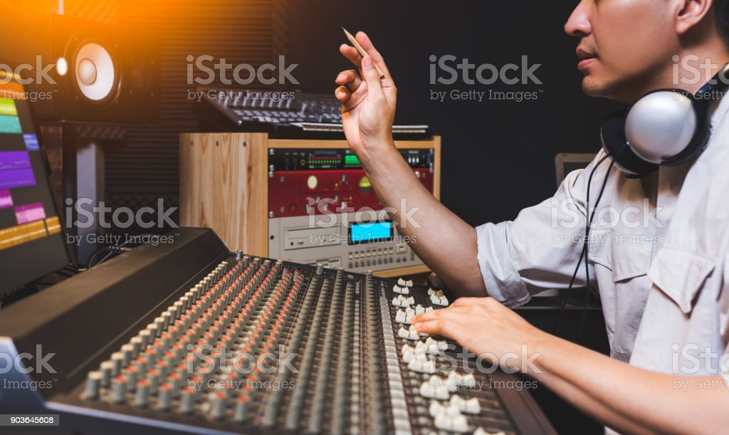asian male music producer working on sound mixer in recording studio stock photo