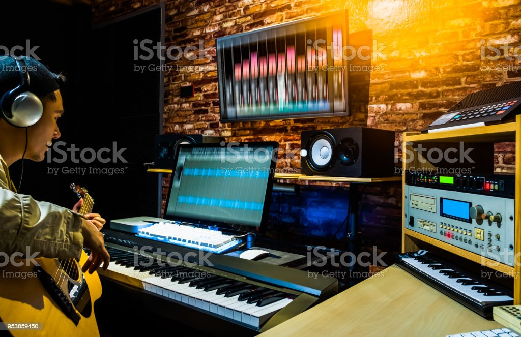 asian male musician recording acoustic guitar track on digital professional audio equipment in home studio stock photo