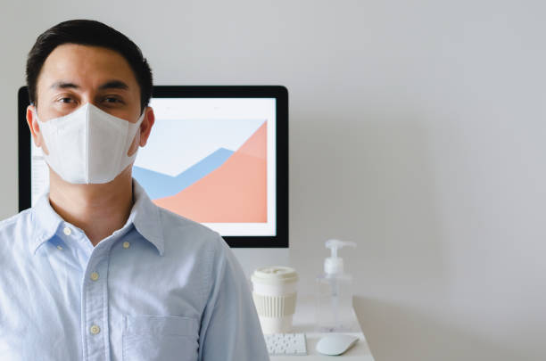 asian male officer wearing mask to protect virus in office room. - businessman covid mask foto e immagini stock