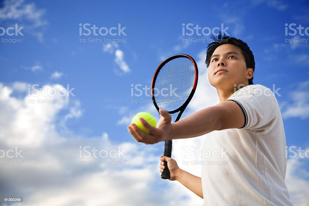 Asian male playing tennis royalty-free stock photo