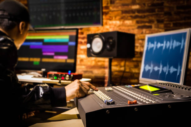 asian male professional sound engineer working in digital recording, broadcasting, editing studio. focus on mixer fader stock photo