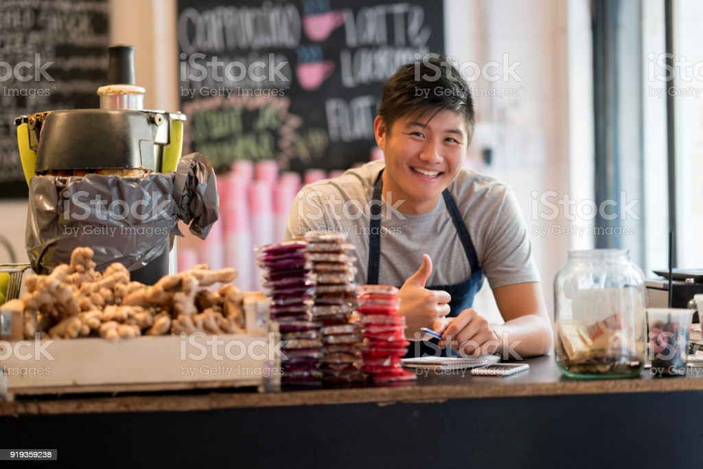 Asian male sales clerk working at a healthy food store looking at camera smiling with thumbs up stock photo