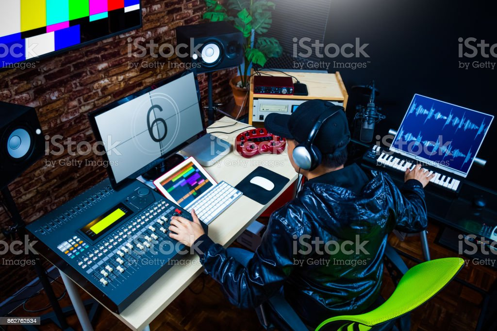 asian male sound engineer working in digital audio & video editing post production studio stock photo